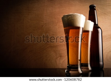Two glasses and Bottle with Beer on the table - stock photo