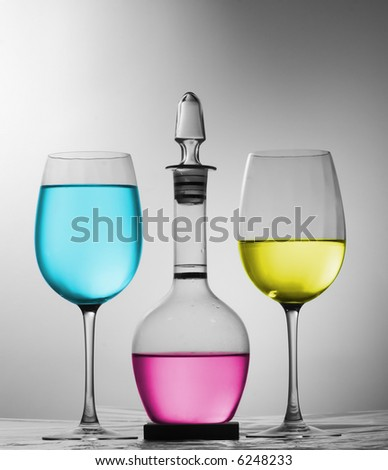 Two glasses and decanter with cyan, magenta and yellow liquid - stock photo