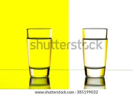 two glasses are isolated on a  yellow  and white background