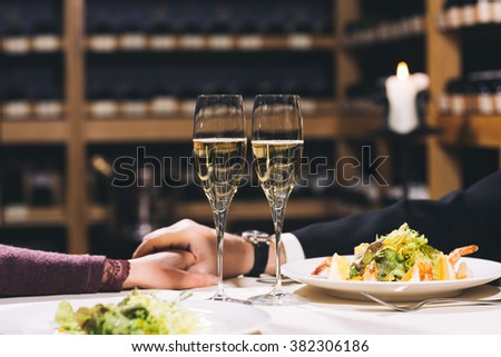 Two glasses for champagne on the table with white tablecloth. Shelves with vine and candles are on background.