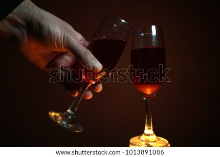 Two glasses. Male hand. Illumination from below. Red wine. Dark background. Romantic setting. The theme of the Valentine's Day, Christmas, New year. Date. Background. Retro. Vintage style. Design elem