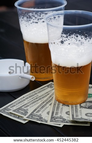 Two glasses of beer, fan-shaped dollars and ash tray with   - stock photo