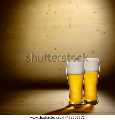 Two glasses of beer on wood background with copyspace