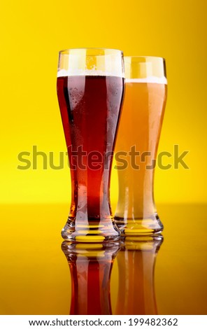 Two glasses of beer over a bright yellow background