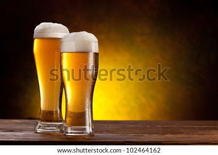 Two glasses of beers on a wooden table. Dark yellow background. - stock photo
