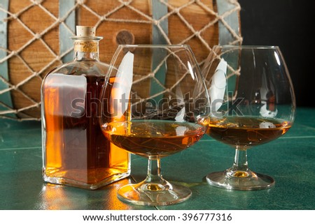 Two glasses of brandy and bottle on a green table top, against a background of old barrels - stock photo