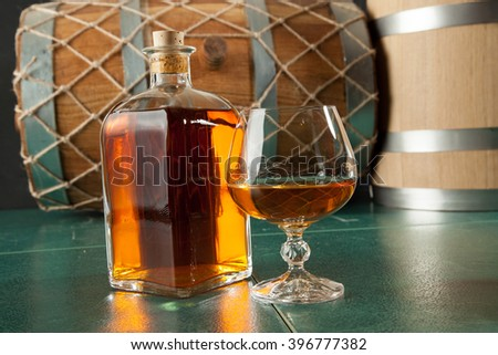Two glasses of brandy and bottle on a green table top, against a background of old barrels