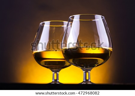 Two glasses of brandy on a dark wood table over a yellow lit background