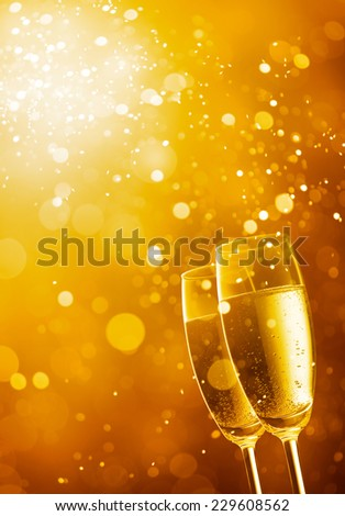 two glasses of champagne against gold bokeh background - stock photo