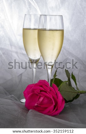 Two Glasses of Champagne and a Single Red Rose - stock photo