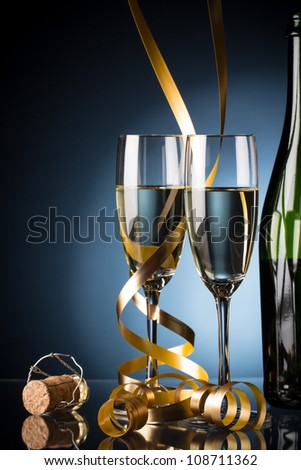 Two glasses of champagne and bottle on blue background with serpentine - stock photo