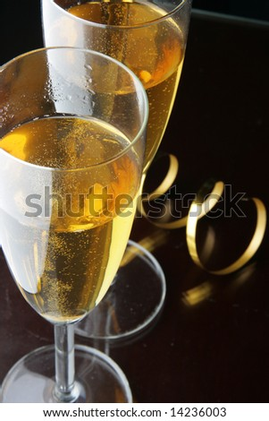 Two glasses of champagne and gold streamer over black background - stock photo
