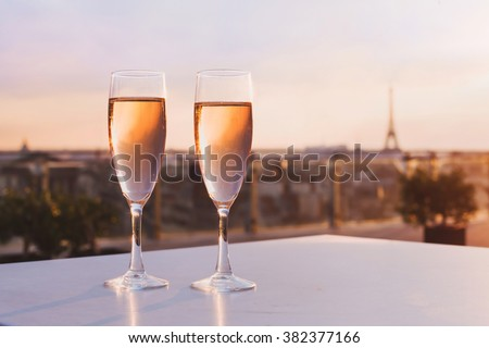 two glasses of champagne at rooftop restaurant with view of Eiffel Tower and Paris skyline, luxury romantic dinner for couple - stock photo