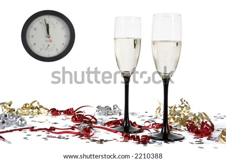 two  glasses of champagne between confetti and streamer and in the background a clock on the verge of midnight - stock photo