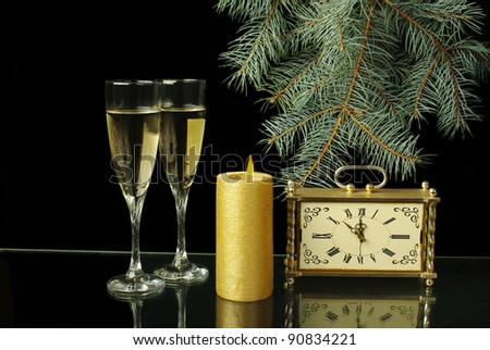 Two glasses of champagne, candle and old clock.