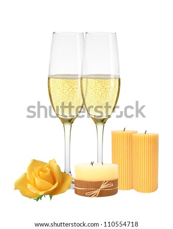 Two glasses of champagne, candles and yellow rose isolated on white background