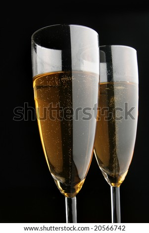 Two glasses of champagne close-uo over black background - stock photo