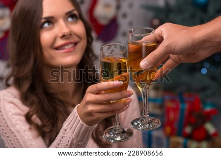 Two glasses of champagne in hand of beautiful attractive brown haired girl sitting  near  fir tree and heap of  presents  in different gift  wrapping dressed in beige knitted jacket
