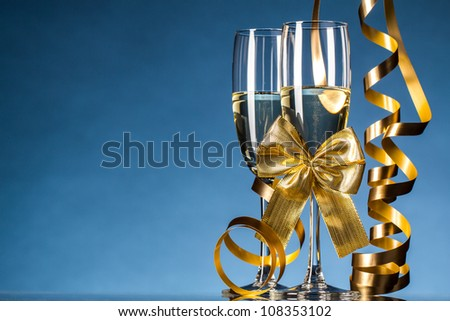 Two glasses of champagne on blue background - stock photo