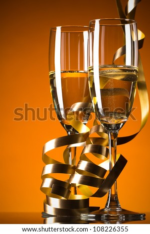 Two glasses of champagne on orange background