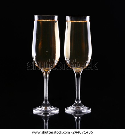 two glasses of champagne over black background