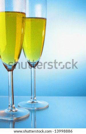 Two glasses of champagne over blue background - stock photo