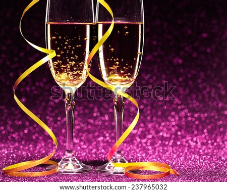 two glasses of champagne ready for christmas celebration, on purple background - stock photo