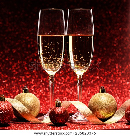 two glasses of champagne ready for christmas celebration, on red background - stock photo
