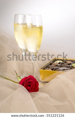 Two Glasses of Champagne, Single Red Rose and a Box of Chocolates, Ready for Valentines Day - stock photo