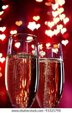 two glasses of champagne with a red background with blurred lights - stock photo