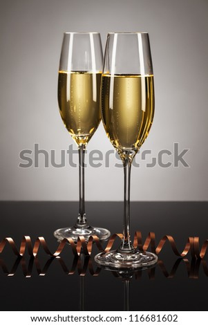 two glasses of champagne with a streamer on a mirror with a spot light background - stock photo
