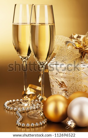 two glasses of champagne with christmas balls and a christmas present - stock photo