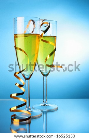Two glasses of champagne with gold streamer over blue background - stock photo