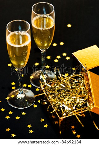 Two glasses of champagne with golden gift box - stock photo