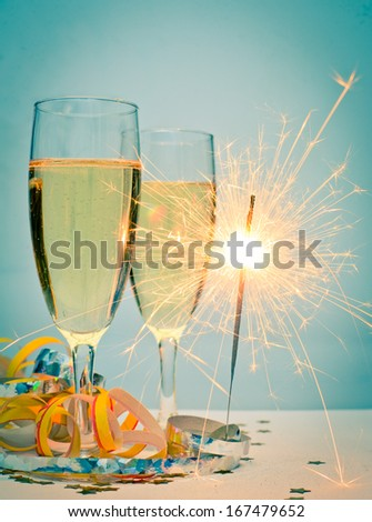 Two glasses of champagne with ribbons and burnning sparkler - stock photo