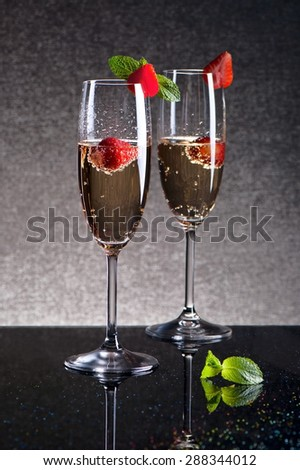 Two glasses of champagne with strawberries on a black table, shot in low key  - stock photo