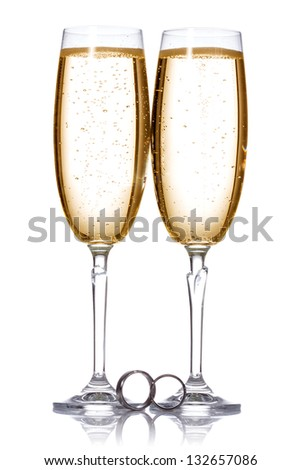 Two glasses of champagne with wedding rings. - stock photo