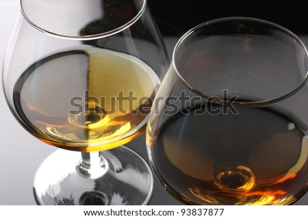 Two glasses of cognac on grey background closeup - stock photo