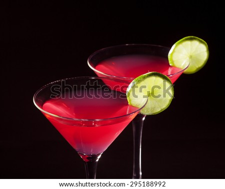 Two glasses of cosmopolitan cocktail on a black background. - stock photo