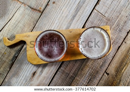 Two glasses of dark amber beer against a wooden rustic cutting board on textured background, top view. - stock photo
