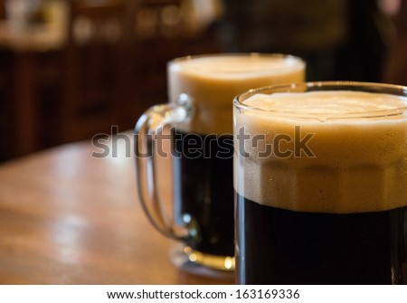Two glasses of dark beer on table - stock photo