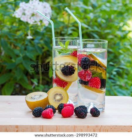 Two glasses of delicious refreshing drink. Infused water with berries, golden kiwi and mint. - stock photo