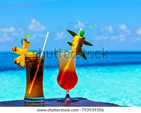 Two glasses of drink are on a beach table (Maldives, The Indian Ocean)