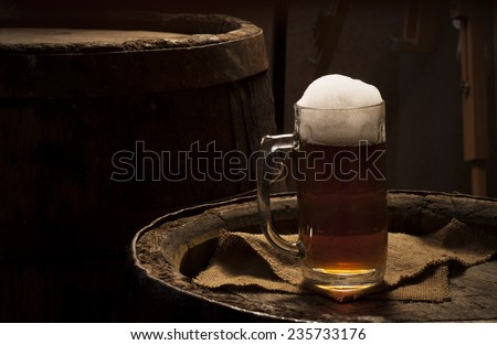 Two glasses of fresh foamy beer on a table in a vintage beer cellar with a barrel in the background