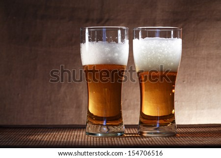 Two glasses of freshness beer with foam on gray canvas background - stock photo