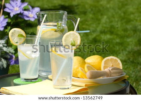 Two glasses of home made iced cold lemonade and pitcher on hot summer.