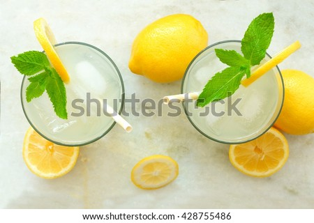 Two glasses of lemonade with mint, overhead view on a white marble background