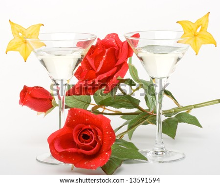 Two glasses of martini, red rose and slice of carambola on a white background