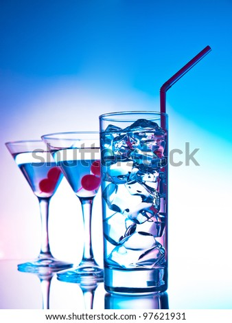 Two glasses of martini with red cherries and a glass of clear cocktail - stock photo
