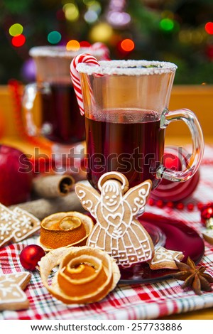 Two glasses of Mulled wine decorated with sugar rim and candy along with spices, fruit, gingerbread cookies and Christmas decorations on checkered red and green cloth.